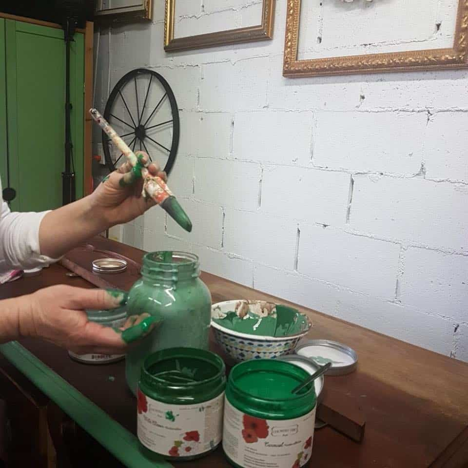 Two containers of Country Chic shades of green paint and hands holding a paintbrush mixing the two colours into a mason jar to create a custom colour